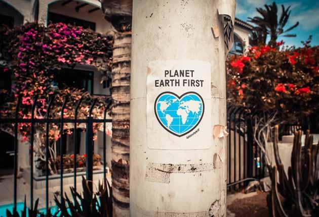 Columna con un cártel en el que pone planet earth first con un jardín de fondo