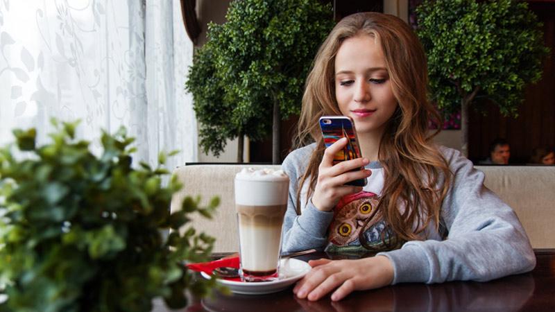 mujer mira telefono mientras toma cafe